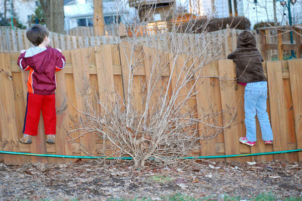 Zwei Kinder schauen bei den neuen Nachbarn über den Zaun