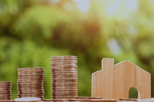 Mietkaution: Geldhaufen und Holzhaus