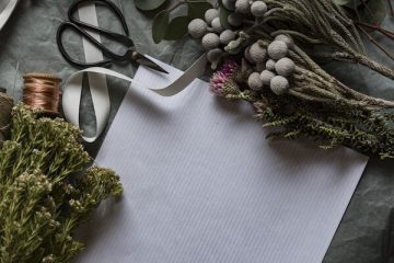 Papier, Schere und Blumen auf einem Tisch