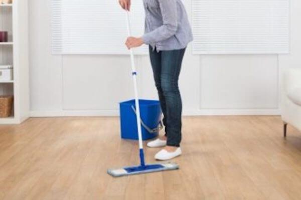 Person die den Boden reinigt