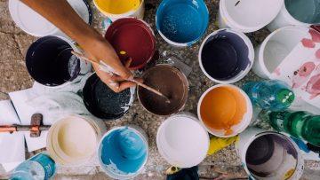 Ganz viele Farben auf einem Tisch um damit eine Wand zu streichen