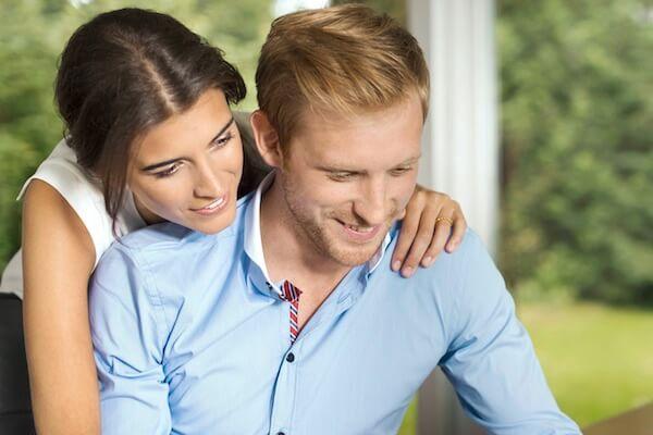 Ein glückliches Paar sitzt am Tisch und informiert sich am Computer über Zusatzversicherungen