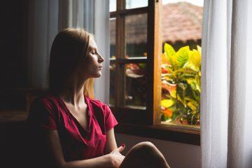 Eine junge Frau sitzt am Fenster und genisst die frische Luft beim Lüften