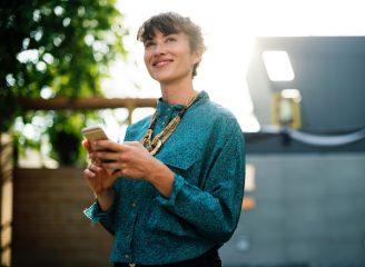 Junge Frau mit Smartphone hat die Vorteile von MOVU entdeckt