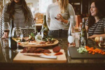 Freunde essen und trinken zusammen bei einer Einweihungsparty nach einem Umzug