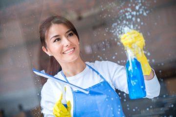 Eine junge Frau putzt ein Fenster