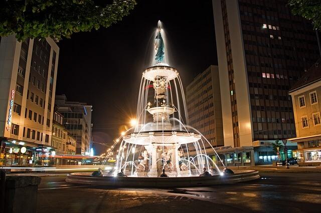 Belle fontaine à La Chaux de Fonds, illuminée la nuit.