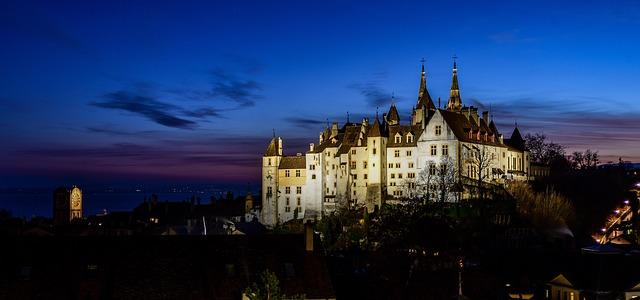 Blick auf ein Schloss in Neuenburg, das in der Nacht beleuchtet wird.