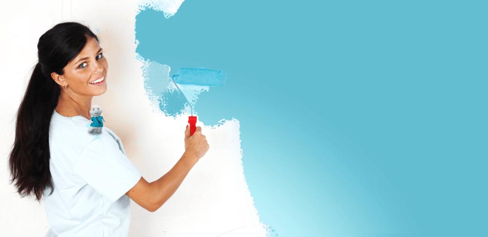 Frau streicht eine Wand Blau an.