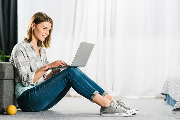 Frau mit Ihrem Laptop auf den Knien.