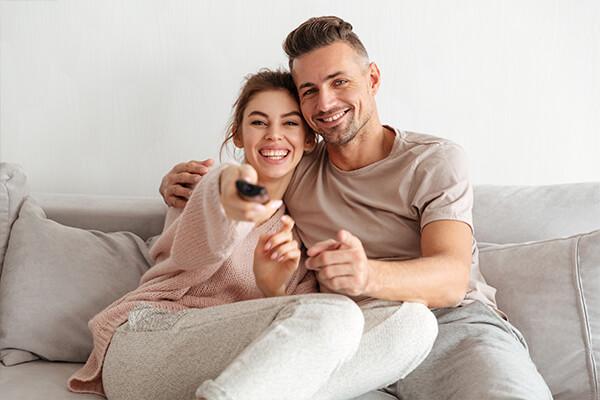 Man und Frau druecken auf der TV-Fernbedienung herum.