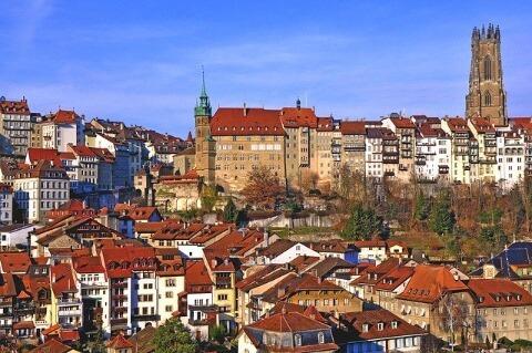 Sicht auf die Stadt Fribourg (Freiburg) mit Sonnenstrahlen.