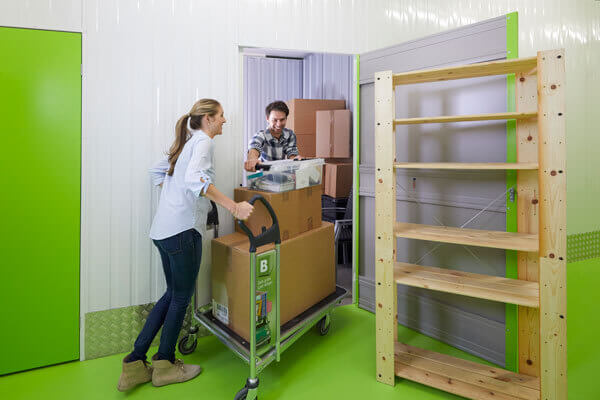 Zwei Personen versorgen Kartons in einen Lagerraum von placeb.