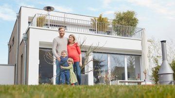 Glückliche Familie vor ihrem Wohneigentum