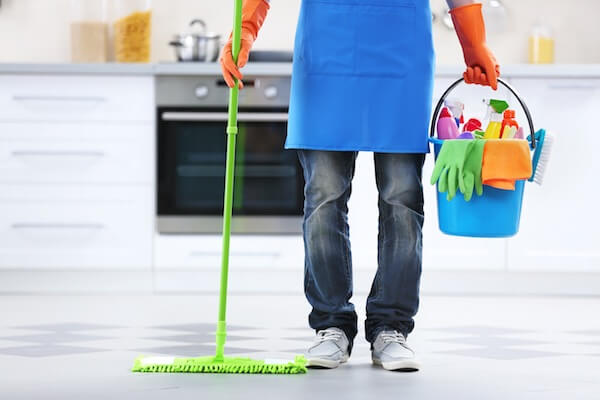 A cleaning lady is cleaning in the kitchen.