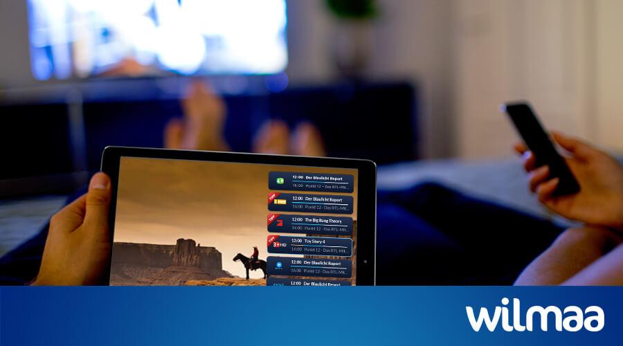 Tablet und TV im Wohnzimmer. Eine Person hält eine Fernbedienung in der Hand