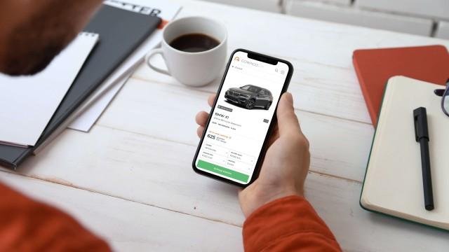 Hand, die ein Smartphone hält. Auf dem Bildschirm wird ein Auto zum Leasen angezeigt.