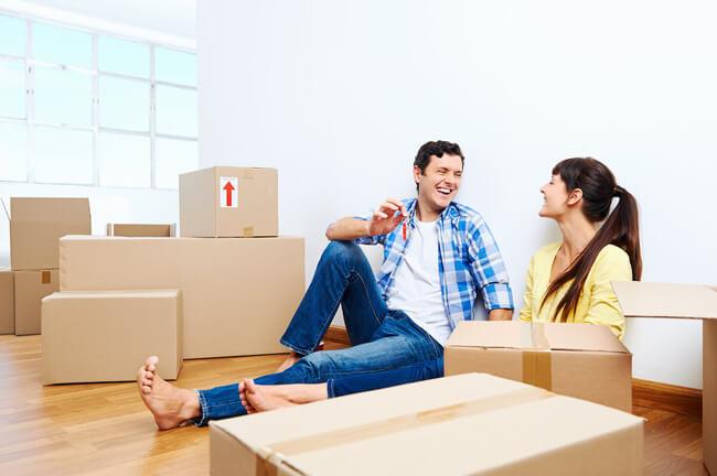 Von einer Umzugsfirma in Rheintal gepackte Umzugskartons und ein Paar lächeln sich gegenseitig an.