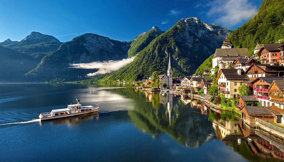 Bild auf einen See, ein fahrendes Schiff und die Alpen.